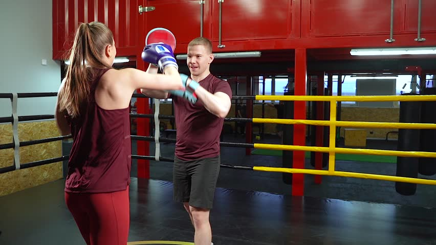Male boxing instructor using boxing kick pads when training young woman in the ring | Shutterstock HD Video #1024151564