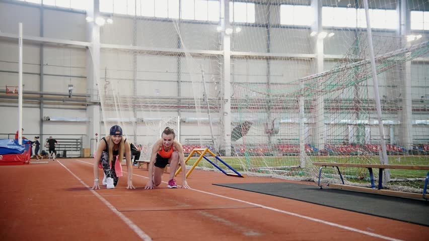 Two young women start running in indoors sports arena | Shutterstock HD Video #1024169174
