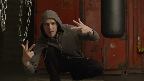 Charismatic gangster rapper in hoodie making cool hand gesture while sitting in abandoned building. Urban style man in hooded sweater gesturing with positive and cheerful look in back-block gym.