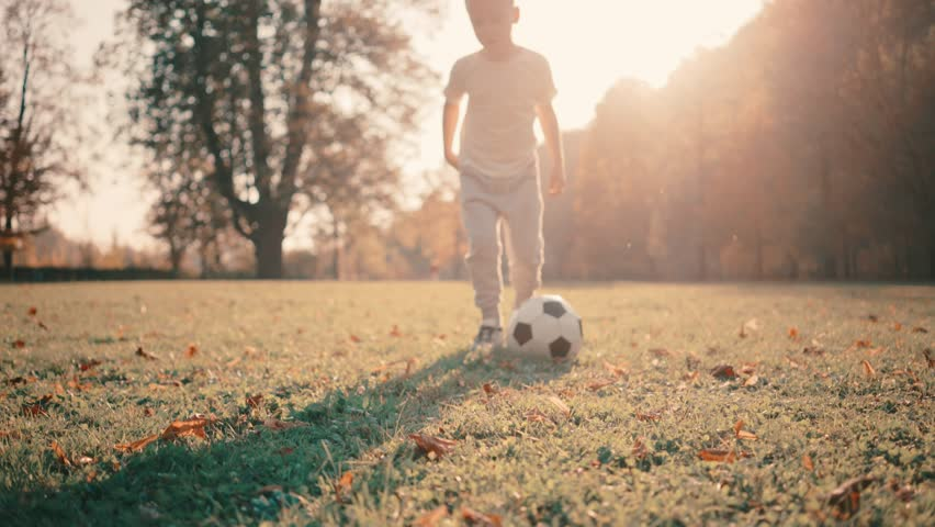 Footballer child players in dynamic action funny play on the sand in football in summer sunny day under sunlight.  | Shutterstock HD Video #1024278314
