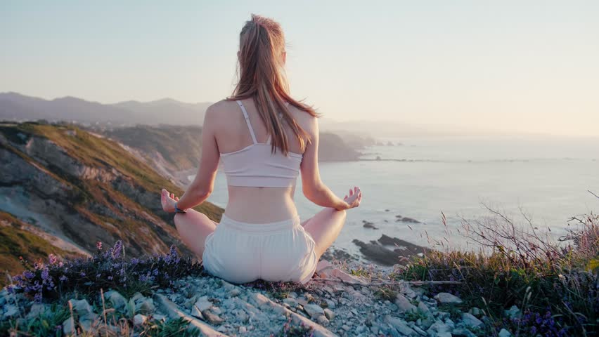 Beautiful and healthy female breathing gently and sits in pose of lotus or sukhasna meditating or practicing yoga and pranayama Get in touch with spiritual side Relax body and mind in nature outdoors | Shutterstock HD Video #1024301834