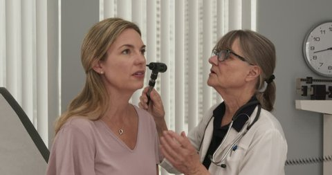 Senior doctor using otoscope on female Caucasian patient to look in ears in exam room. Middle aged woman visiting primary care physician at clinic or hospital. Slow motion 4k