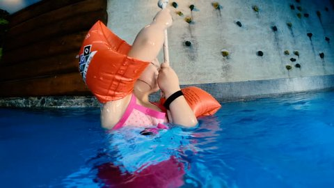 Bansko, Bulgaria - 10 June, 2017: Slow motion of Little girl putting effort to climb the hanging rope into the pool