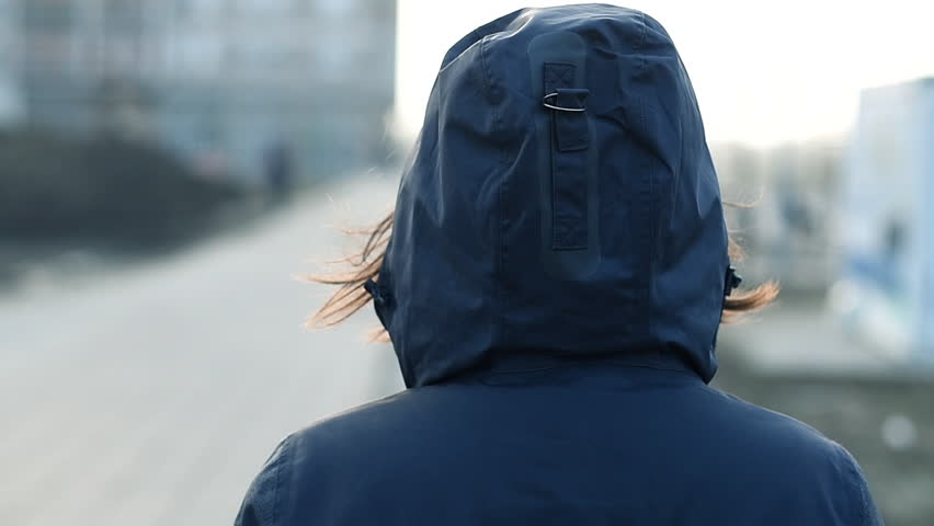 Rear view of hooded female person walking the city street in cold winter afternoon, slow motion