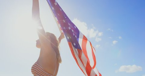 Low angle view of young Caucasian woman holding a American flag on the beach. American flag fluttering in her hands