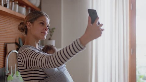 happy mother taking selfie photo with baby using smartphone at home sharing motherhood lifestyle online enjoying social media connection