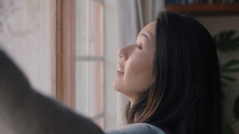 beautiful asian woman opening curtains looking out window ready for fresh new day feeling rested