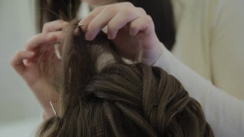 A young woman sits in a hairdresser's armchair: a hairdresser does a hair styling. A young fair-haired woman came to the beauty salon to make a stylish hairstyle.