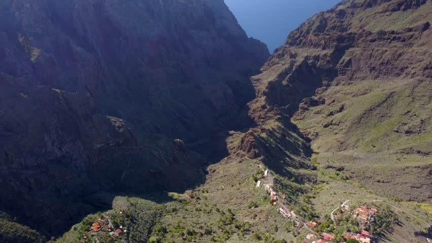 The small road in the center of the mountain ranges in Tenerife Spain with the tall mountains on the side | Shutterstock HD Video #1024485584