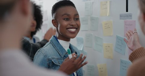 african american business woman using sticky notes brainstorming with colleagues in meeting team leader sharing creative problem solving ideas for solution enjoying teamwork in startup office