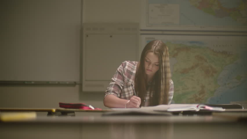 Female student in classroom surrounded by textbooks writes in her notebook working on school work in a classroom setting with map behind her. Filmed with Arri Alexa Mini | Shutterstock HD Video #1024494824