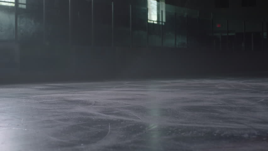 Hockey player skates into frame in hockey arena stick handling and practicing with hockey stick. Filmed with Arri Alexa Mini