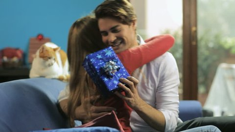Happy husband and wife, caucasian heterosexual couple hugging on sofa while giving gift at home
