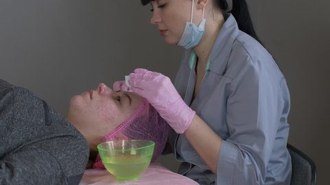 Doctor cosmetologist makes Rejuvenating facial pilling procedure for tightening and smoothing wrinkles on face skin of beautiful, young woman in beauty salon.Cosmetology skin care.