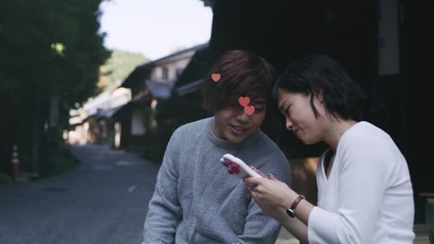 Young couple sitting outside and looking on the girlfriend's phone with emojis flying from phonein Kyoto, Japan. Close up to wide shot on 4k RED camera on a gimbal.