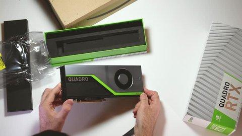 Paris, France - Feb 20, 2019: Man admiring the latest Nvidia Quadro RTX 5000 workstation professional video card GPU adapter unboxing