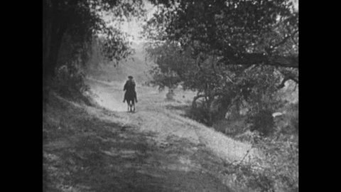 1920s: Cowboy rides horse down tree-lined dirt road. Stagecoach rolls down dirt road. Indians talk on horseback. Indian chief points.
