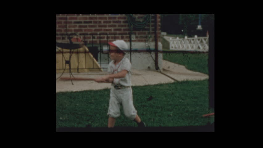 1958 Young boy in baseball uniform bats baseballs