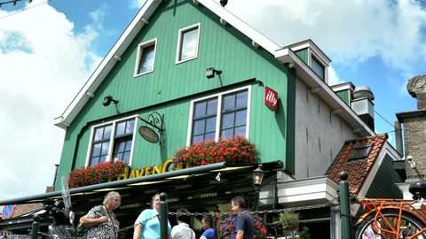 Volendam, Netherlands -August 18, 2018: Tourists walking near typical small Dutch houses with beautiful facades in Volendam, 4K