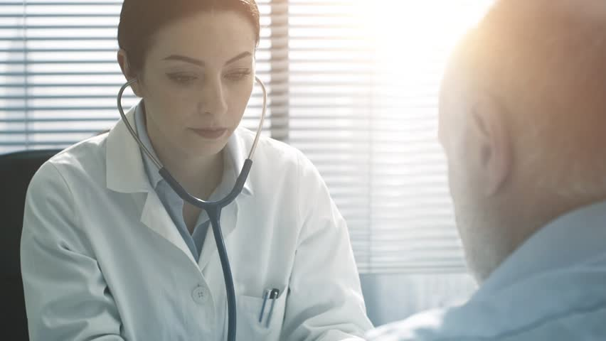 Professional female doctor sitting at office desk and measuring blood pressure of a patient, healthcare and prevention concept | Shutterstock HD Video #1024932794