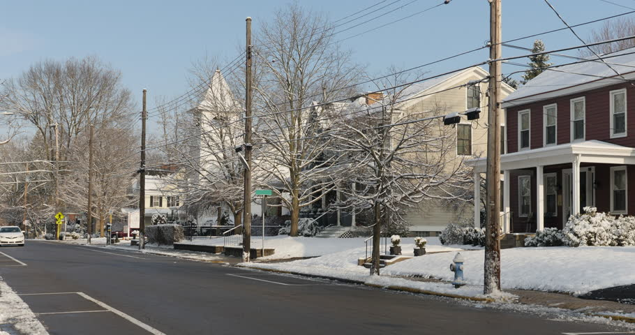 A daytime or morning winter establishing shot of traffic driving in a small town's residential district.   | Shutterstock HD Video #1024936124