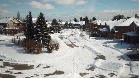 Aerial drone footage flying low over suburban streets in North America while houses and streets are covered in snow on a bright sunny day.