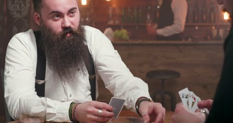 Revealing shot of a young man with big beard playing a card game with a rival. Shot from behind the back revealing the face of a young hipster with stylish beard.