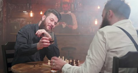 Two young hipsters clinking glasses of whisky and drink at a chess game in a pub. A conversation between two friends in a bar.