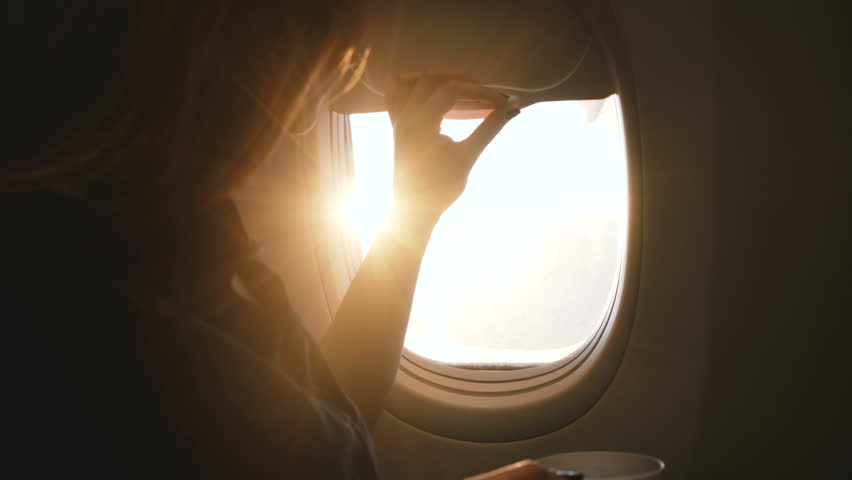 Close-up shot of happy female passenger opening airplane window, enjoying hot drink and amazing sunny view during flight | Shutterstock HD Video #1024987604