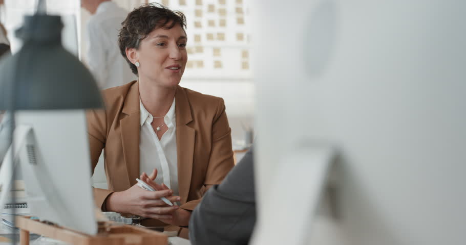 Young business woman chatting to intern discussing job interview colleagues having conversation in office enjoying teamwork