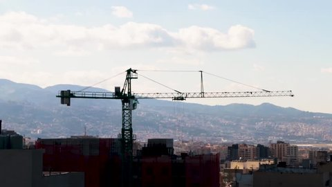 Crane moving parts to a building construction site. Overlooking the south Lebanese Mountains.