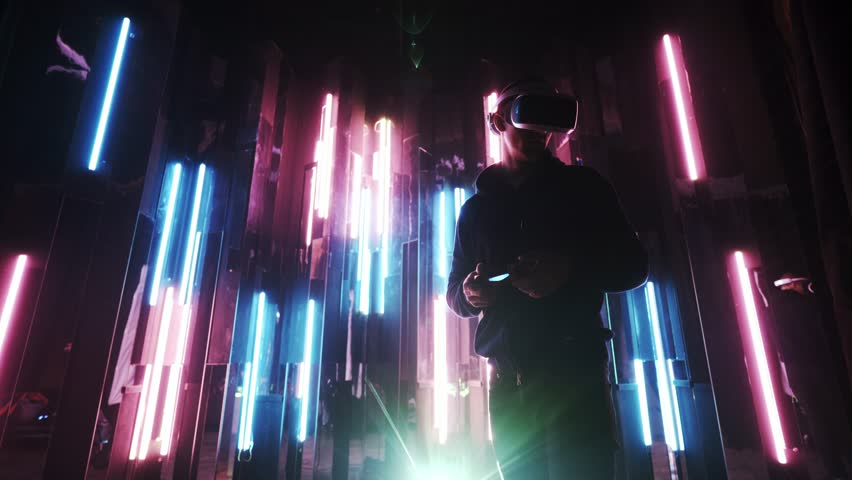 Young man using joystick in hands and VR headset on head playing in dark space on background colored neon lights. | Shutterstock HD Video #1025065364