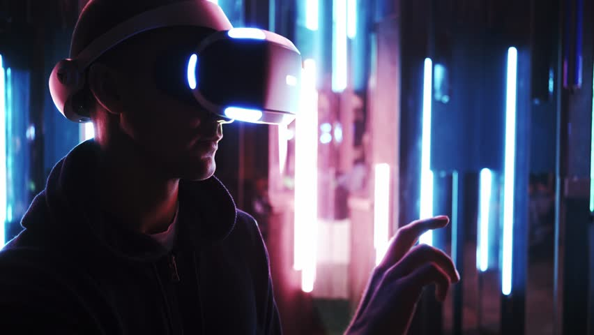 Side view man using VR headset moving hands side to side ,scrolling virtual windows or pages in dark space on background colored neon lamps | Shutterstock HD Video #1025065394