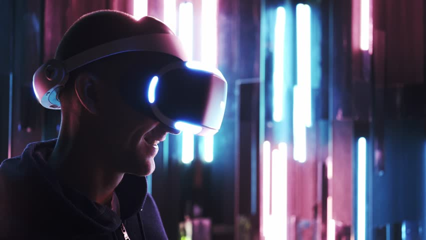 Portrait men in modern VR headset turning head around, looking virtual reality in google's in dark space at background colored neon lamps