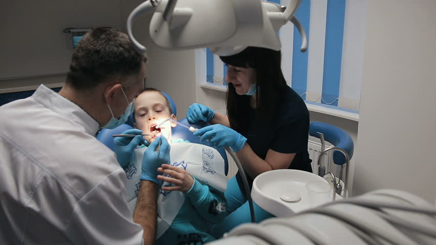Male dentist with assistant in work. Patient child boy in dental clinic | Shutterstock HD Video #1025097794