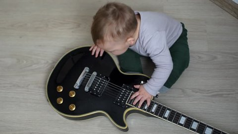 Curious little boy sees guitar for the first time. Little cute baby with interest pushes a guitar on the floor.