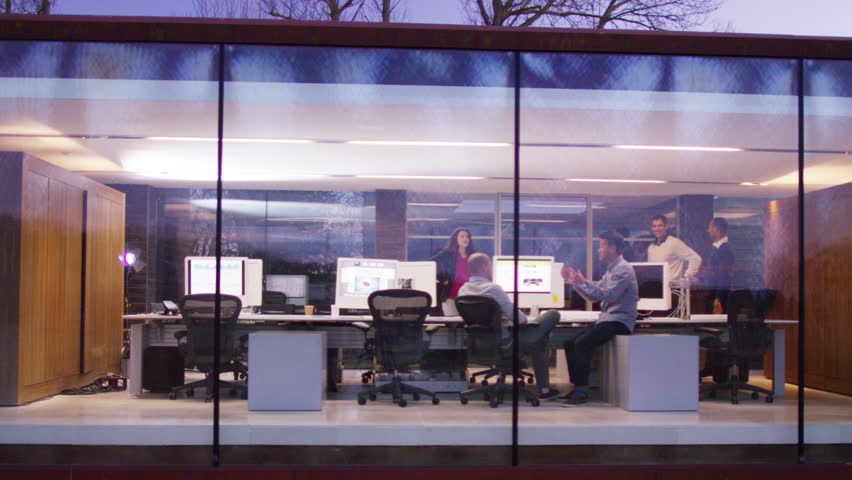 4K Creative business team working together in modern office, seen through the glass from the outside looking in