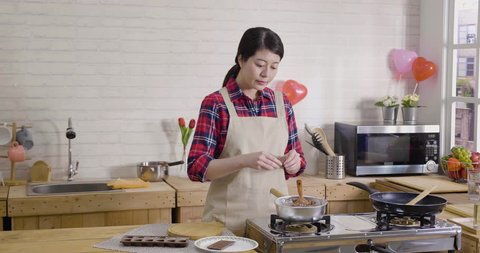 wife in apron standing in modern wooden kitchen breaking dark chocolate into pieces. asian female chef baker mixing sweet delicious organic melted cocoa cream in bowl in hot pot on stove stirring.