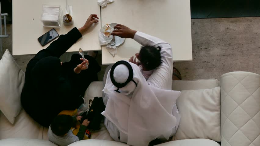 Top view of an Arab family sitting on a sofa eating dessert  | Shutterstock HD Video #1025177174