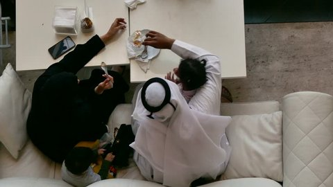 Top view of an Arab family sitting on a sofa eating dessert