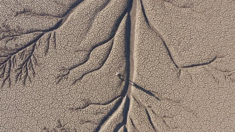4K aerial zoom out view of a devastated farmer walking across the patterned cracked mud surface of a dry dam due to drought from climate change and global warming