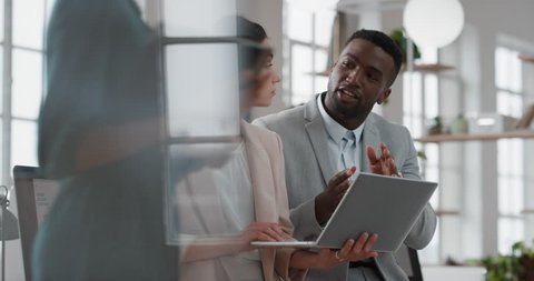young team leader black woman brainstorming with businessman colleague using laptop computer showing ideas pointing at screen working together in office
