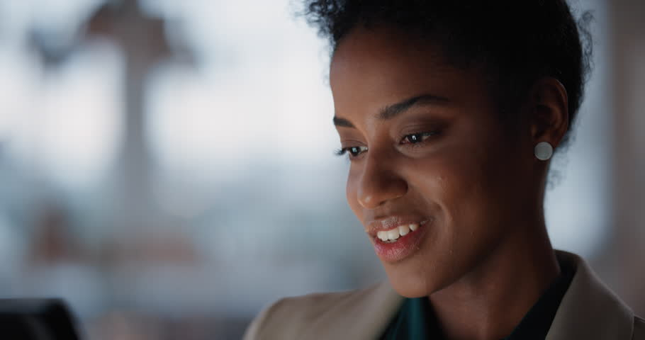 Beautiful black business woman using tablet computer working late in office browsing information looking at data on digital touchscreen | Shutterstock HD Video #1025212004