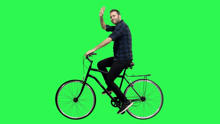 A Cute man riding a bicycle over a green screen, looking around and upwards, waving hello. No motion blur for optimal keying. | Shutterstock HD Video #1025264624