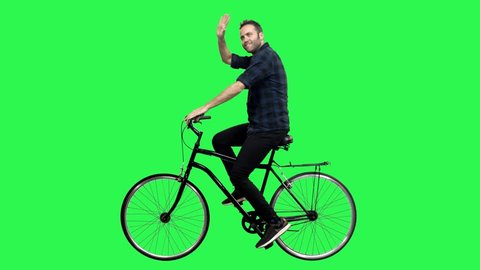 A Cute man riding a bicycle over a green screen, looking around and upwards, waving hello. No motion blur for optimal keying.