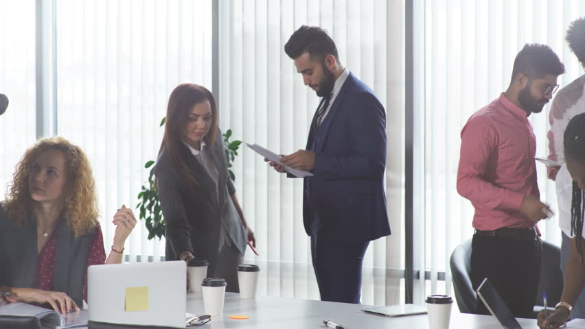 Multiracial, business people talking in break, communicate and have consultation with the application form in hand over panoramic windows. | Shutterstock HD Video #1025276054