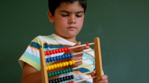 Front view of cute Caucasian boy learning mathematics with abacus against green board in classroom. He is counting beads 4k