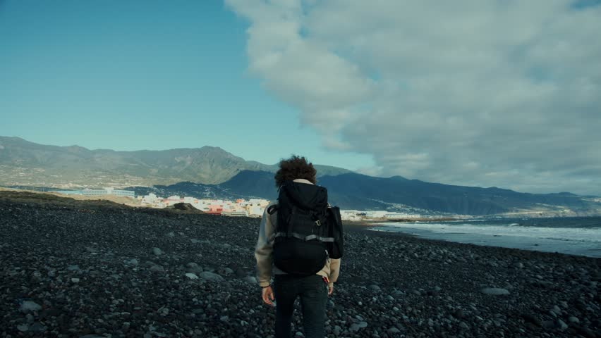 Epic and inspiring dreamy slow motion shot of camera follow adventurous young traveller, hitchhiker, camper or bikepacker walk towards incredible mountain landscape on beach, look back