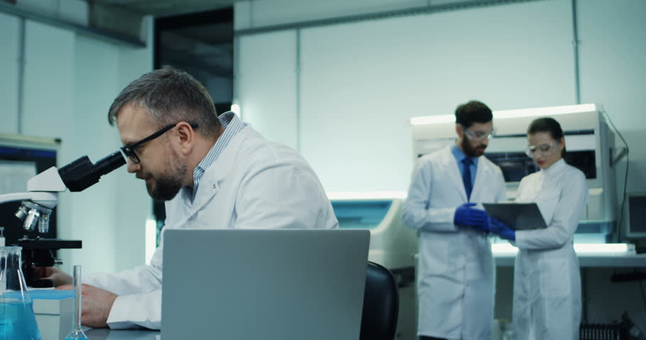 Close up of the Caucasian man in glasses, medical researcher, looking in the microscope while doing some analysis and typing them in the laptop computer at the laboratory. | Shutterstock HD Video #1025368994