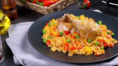 Arroz con pollo. Baked pieces of chicken with bone, rice with paprika and peas. Black background. Served on black plate or spanish pan.  Cooking, steaming, eating, watching. Slow motion.